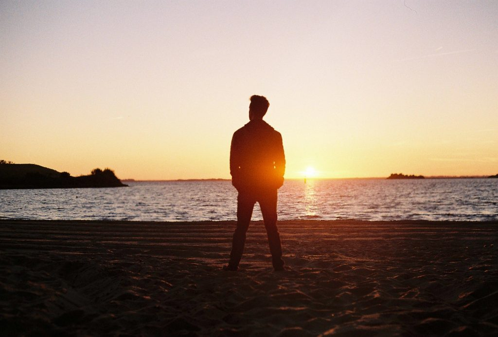 silhouette of man in front of sunset